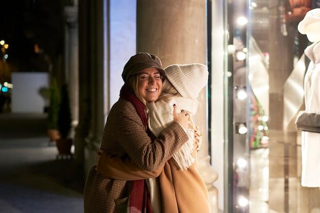 두 여성이 포옹으로 서로 따뜻하게 인사합니다. 밤에 도시에서 함께, 재회를 위해 행복합니다.