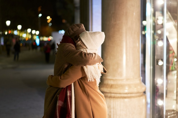포옹으로 서로 인사하는 두 여자. 밤에 도시에서 함께.