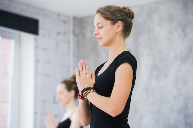 Two women in gym class doing relaxation exercise at yoga class