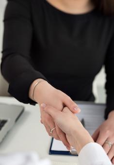 Рукопожатие двух женщин в офисе крупным планом. деловые женщины, пожимая руки. концепция серьезного бизнеса, партнерства и сотрудничества. партнеры заключили сделку и скрепили ее застежкой. официальный приветственный жест