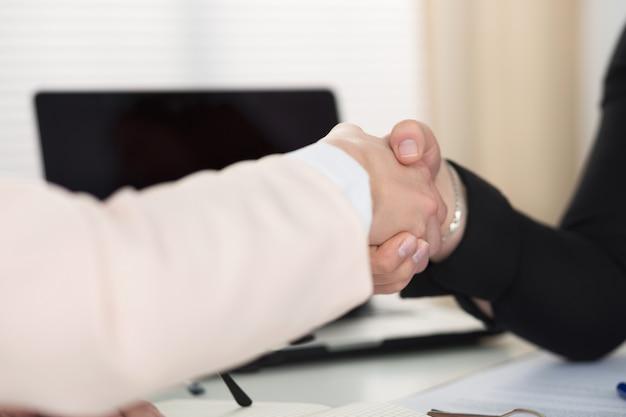 2人の女性がオフィスのクローズアップで握手します。握手するビジネスウーマン。真剣なビジネス、パートナーシップ、コラボレーションのコンセプト。