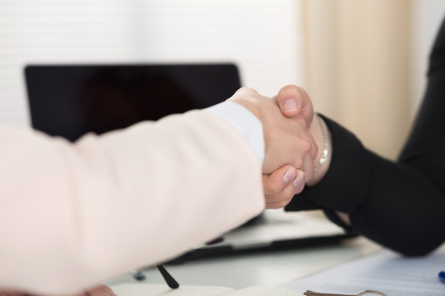 Two women handshake in office closeup. businesswomen shaking hands. serious business, partnership and collaboration concept.