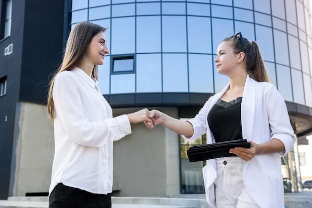 大企業センターの外で握手する2人の女性。成功した女性が取引をする