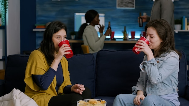 ソファでリラックスしながらハイト5を与えるホームパーティーでぶらぶらしている2人の女性