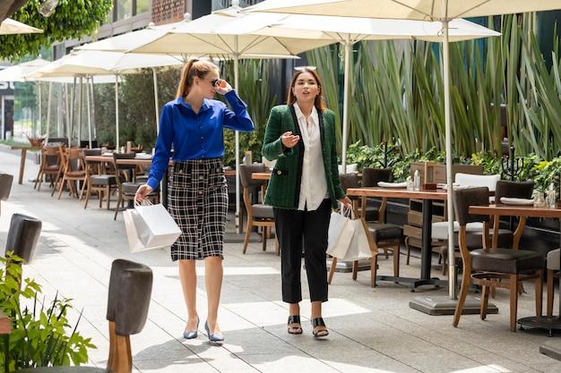 買い物をした後、2人の女性が街の通りを楽しく歩きます