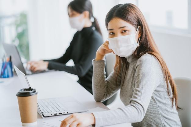 두 명의 여성이 근무 시간 동안 마스크를 착용해야 전염병 발생시 안전을 유지할 수 있습니다.