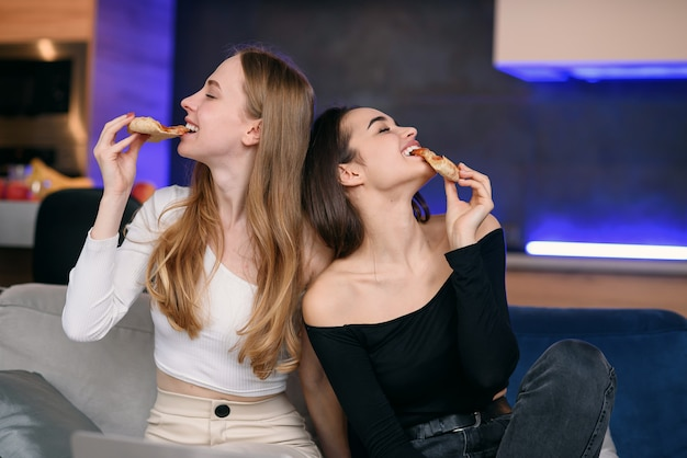 Two women having fun at home, opening pizza box, food delivery, home party