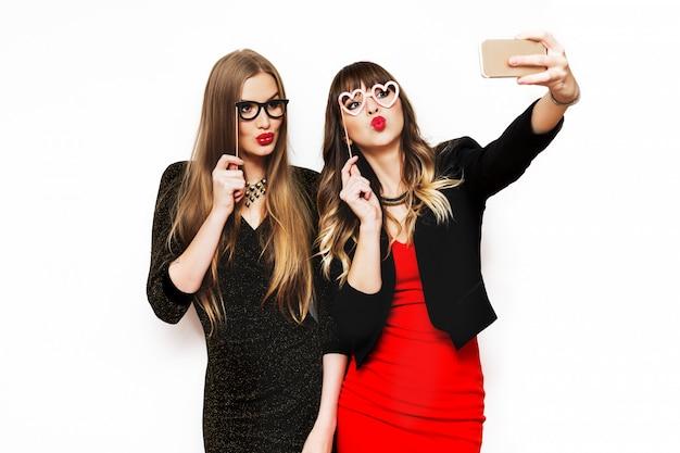 Due donne che si divertono insieme, facendo autoritratto
