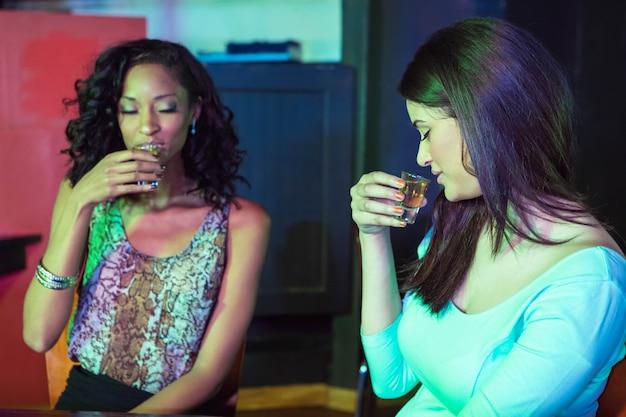 Two women having tequila at nightclub