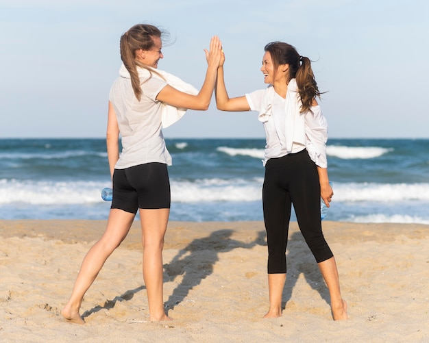 Two women high-fiving while working out on the beach