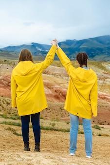 컬러 산의 배경에 손을 잡고 두 여성 등산객