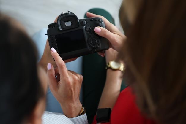 두 명의 여성이 카메라를 손에 들고 버튼을 누릅니다.