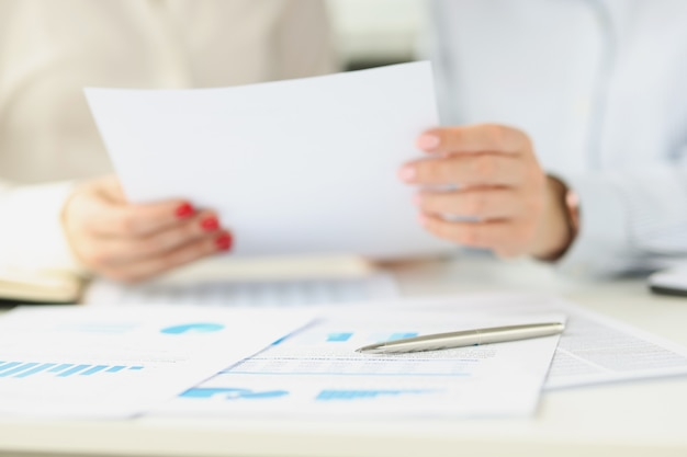 Two women hold a document on table lie charts with business indicators collaboration and
