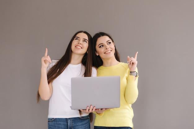 2人の女性が1台のラップトップを持っています。女性は指を持ち上げて魅力的な笑顔をします
