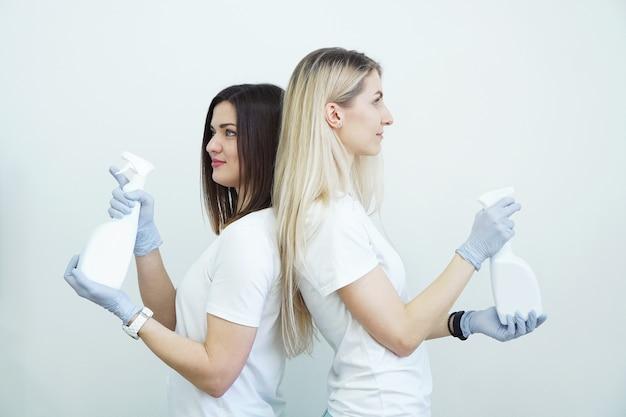 2人の女性が消毒剤または銃のような洗剤でスプレーボトルを保持します健康またはクリーニングの概念白い背景にcovid