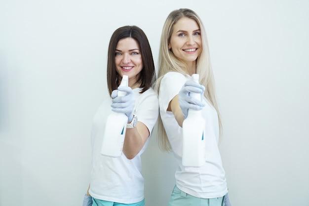두 여자는 흰색 배경에 총 건강 또는 청소 개념 covid와 같은 방부제 또는 세제로 스프레이 병을 개최