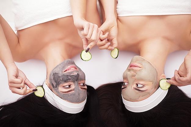 Две женщины держат на лицах кусочки огурца, лежа на кровати