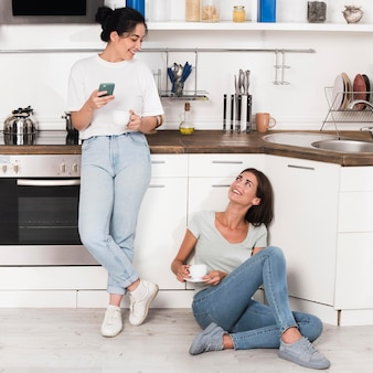 Two women at home in the kitchen chatting over coffee