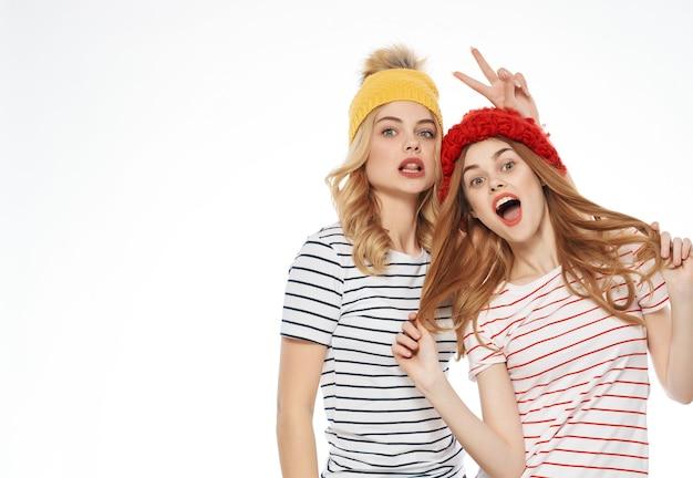 キャップの友情の感情の明るい背景で抱き締める2人の女性。高品質の写真