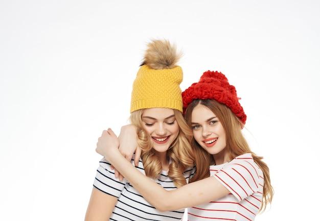 キャップの友情の感情の明るい背景で抱き締める2人の女性