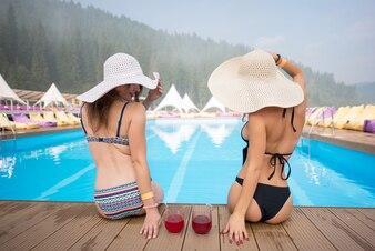 スイミングプールの端に座っている帽子の2人の女性
