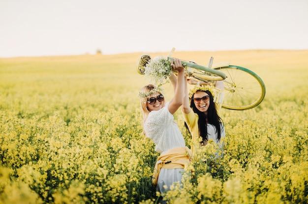 自転車で菜種畑にいる2人の女性が喜んで自然の中を散歩します