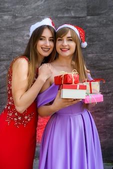 선물 가방을 찾고 우아한 이브닝 드레스에 두 여자. 신년 파티 축하