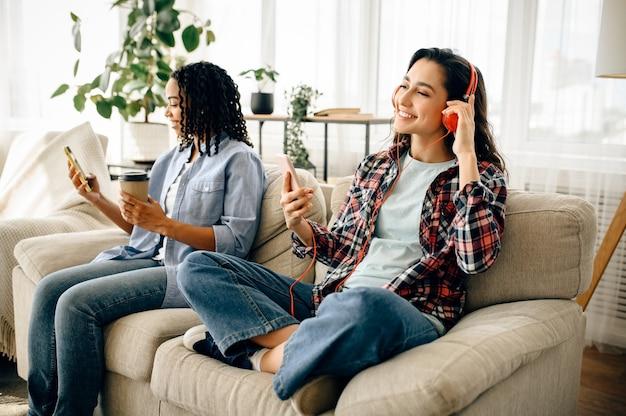 ソファーでヘッドフォンレジャーで2人の女性