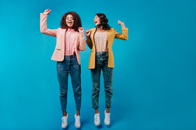 青い壁にジャンプするジーンズの2人の女性