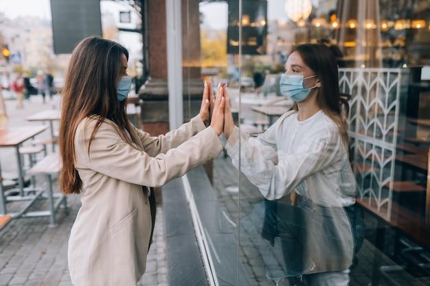 彼らの間の窓の向かい合った保護マスクの2人の女性