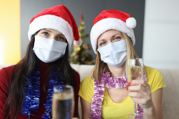 保護用医療マスクを着用した2人の女性がシャンパングラスを持っています