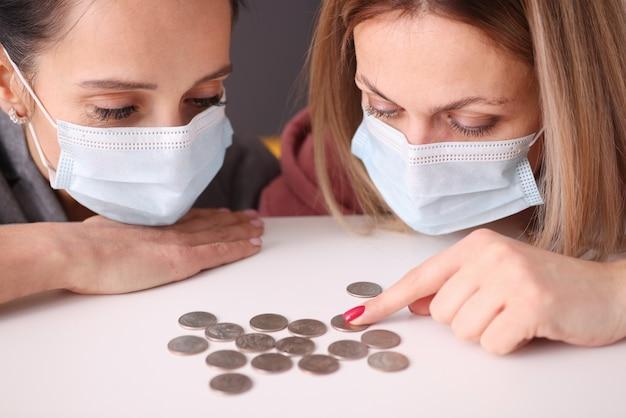 Две женщины в защитных медицинских масках смотрят на монеты на столе. бизнес в условиях пандемии коронавируса
