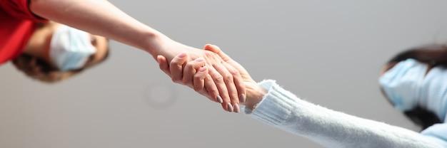 サージカルマスクを着用した2人の女性が握手します。コロナウイルスパンデミックコンセプトにおける安全なコミュニケーション