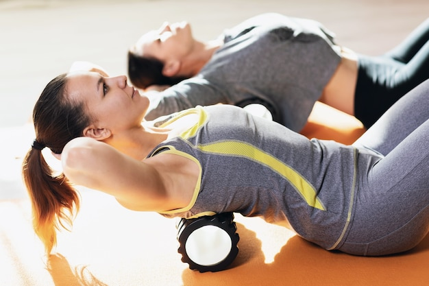 체조 매트에서 건강한 라이프 스타일을 선도하는 운동복을 입은 두 여성이 마사지 롤러를 사용하여 등 근육의 근막 이완을 수행합니다.