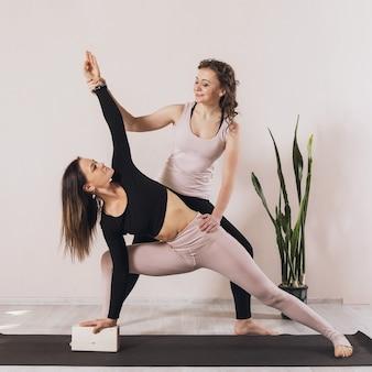Две женщины в спортивной одежде, практикующие йогу, делают низкий выпад на одной ноге с поворотом или позой полумесяца анджанасаны.