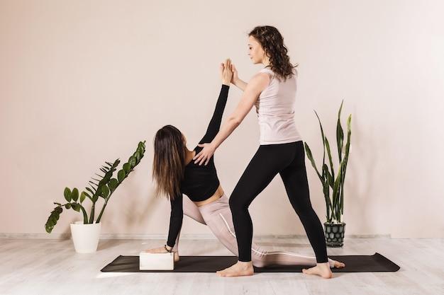 Две женщины в спортивной одежде, практикующие йогу, делают низкий выпад на одной ноге с поворотом или анджанасана, или анджанеясана, или поза полумесяца, или поза молодой луны.