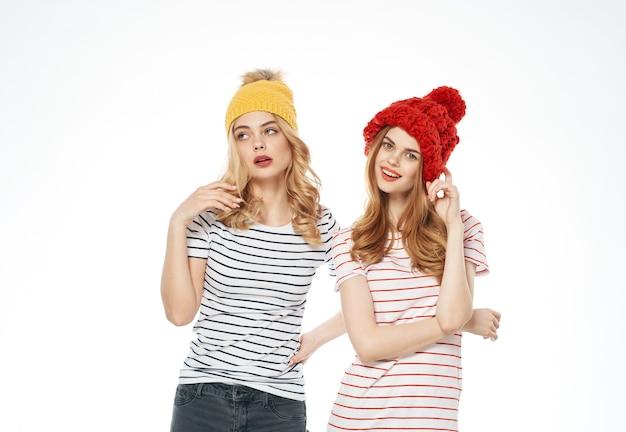 ストライプのtシャツを着た2人の女性、色とりどりの帽子、感情、ファッションスタジオのコミュニケーションがトリミングされました。高品質の写真