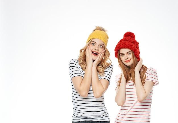 Две женщины в полосатых футболках разноцветных шляпах эмоции от общения студии моды обрезаны. фото высокого качества