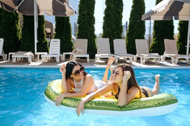 リゾートのプールにある膨脹可能なマットレスで日光浴をするサングラスをかけた 2 人の女性。晴れた日にはプールサイドでリラックスする美しい女の子たち、魅力的な女性たちの夏休み