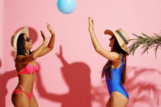 Две женщины в купальниках играют с мячом на розовом