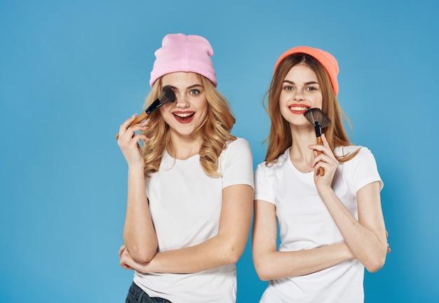 Tシャツ化粧品友情青い背景の2人の女性