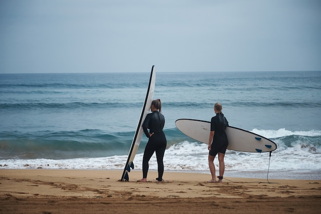 서핑 보드가있는 잠수복을 입은 두 여성이 시원한 여름날 물에 들어갈 준비를하고 있습니다.