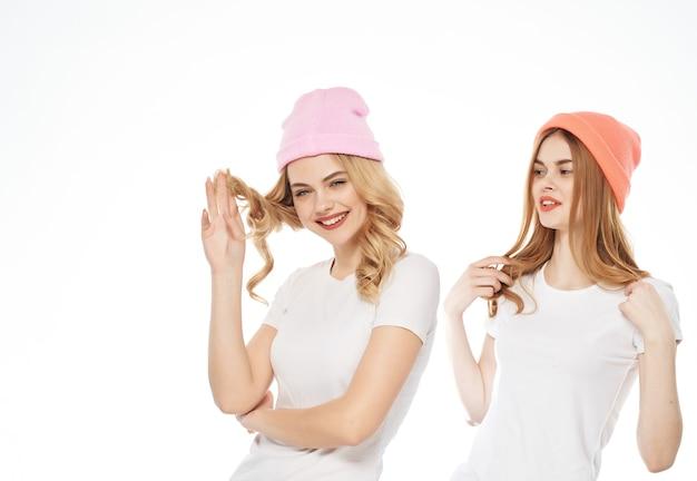 頭の上の白いtシャツの帽子の2人の女性ファッションコミュニケーション明るい背景