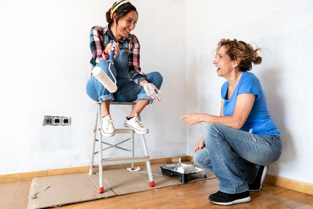 Two women interacting while painting walls white with paint roller loading roller in paint tray