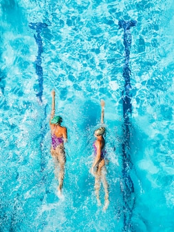 Two women is swimming in a pool, seen from above.