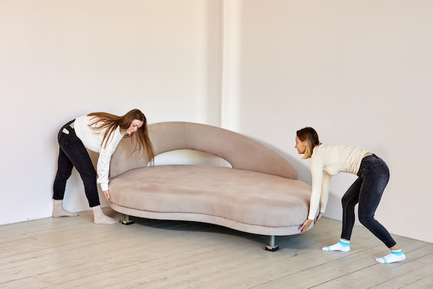 Two women in jeans move sofa in new flat