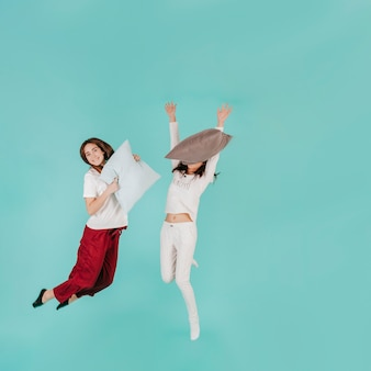 Two women jumping with pillows