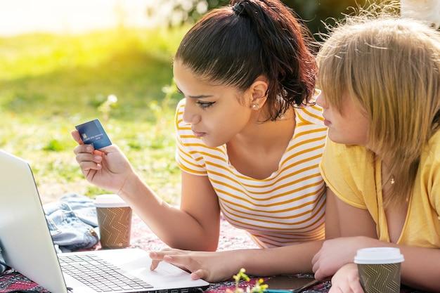 晴れた日にオンラインでコンピューターとクレジットカードを購入している公園で2人の女性ラティーナ