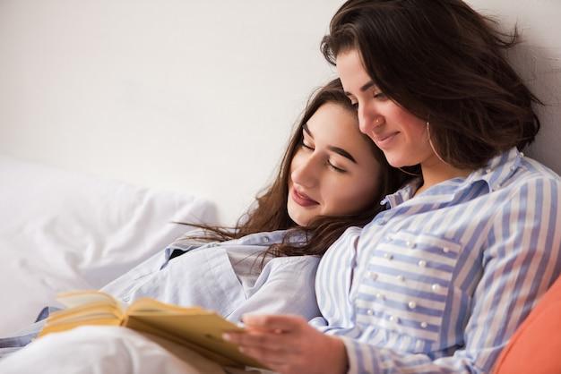 2人の女性が紙の本でベッドに横たわっていた