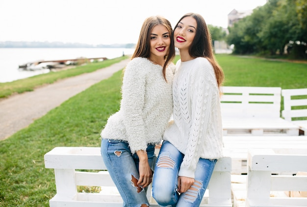 Two women lean on a white bench in the park